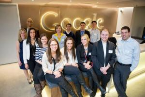 Group of QU students gathers at the front desk during their visit to Google in Cambridge, Massachusetts.